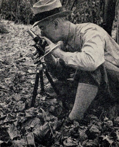 "Photo titled ""Getting a close-up of a flower"" by Wylie Bowmaster. The name of the pictured photographer isn't known. From 1938 handbook. photographer"